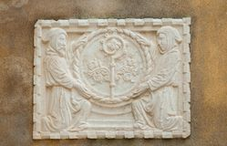 Crosier with two monks. Religious symbols in Venice. Crosier staff between two hooded monks, an ancient stone relief on a wall in the historic center Royalty Free Stock Image