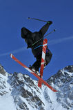 Cross. A freerider skier with crossed skis during a jump royalty free stock images