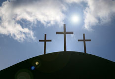 The Cross. Three crosses on a grassy hill with sun-flare and clouds Royalty Free Stock Images