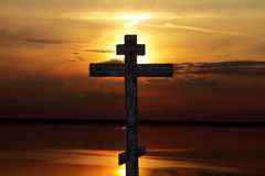 Cross. Wooden cross and sunset over lake Royalty Free Stock Images