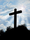 Cross. A cross on a hill top with clouds and sun beams shinning behind it Stock Photo