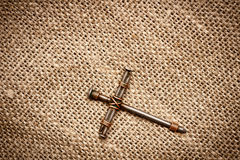 Cross. A cross with nails on canvas background Stock Photo