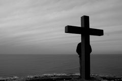 The Cross. Someone behind a cross, staring at the horizon Stock Photography