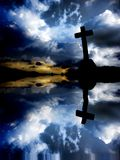 Cross. Silhouette at sunset with water reflection royalty free stock photo