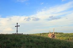 Cross. Christian wood cross on grass overgrown hill (forest colony and windmill beyond Royalty Free Stock Photo