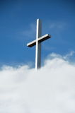 The Cross. Steel Christian cross against blue sky and clouds Stock Images
