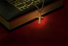 The Cross. A gold cross necklace on a holy Bible stock photography