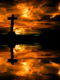 Cross. Silhouette and the clouds at sunset Stock Photography