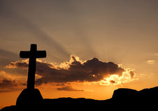 Cross. Silhouette and the clouds at sunset Stock Photos