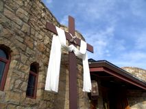The Cross. Cross in front of stone church - draped with white cloth royalty free stock image