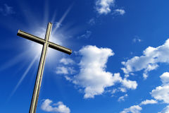 Cross Against the Blue Sky. Wooden high cross with blue sky, clouds and reflection Stock Images