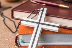 Cross against an old book. Royalty Free Stock Photos