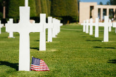 A cross and an american Flag in a military cemetery Stock Photo