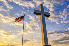 Cross and American Flag at sunset. A worn American Flag flies next to this Cross monument at sunset in Western Kentucky near the convergence of the Ohio and Stock Photo