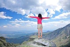Cross arms winner woman at top rock Stock Photos