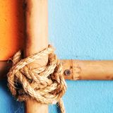 Cross bamboo bars with rope tied on the vintage wall background. Stock Image