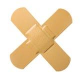 Cross Bandaid. Bandaid in cross shape, isolated white background Royalty Free Stock Images