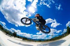 Cross bar. BMX rider jumps while doing cross bar trick Royalty Free Stock Photography