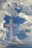 Cross behind clouds. Stone cross behind clouds against blue sky Stock Photography