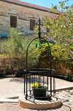 Cross and bell. Over basket with fresh flowers fenced with metal rods Royalty Free Stock Photo