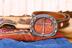 Cross Belt Buckle. Cowboy's cross belt buckle, belt, jeans, shirt and leather chaps in a studio setting Royalty Free Stock Image