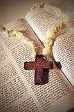 Cross on the Bible. Wooden cross on pearl rosary on an open Bible with text of Resurrection in retro cross-process effect Stock Images