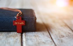 Cross with Bible. Closeup of simple wooden Christian cross necklace on holy Bible Stock Photos