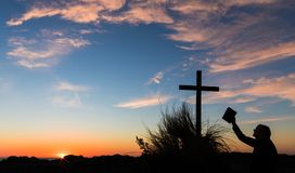 The Cross and The Bible. Man holding up The Bible to a cross on a sand hill, with a wonderful sunset sky royalty free stock photo