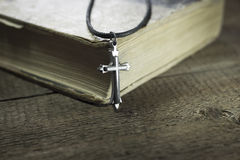 Cross. Bible with a cross on an old wooden table Royalty Free Stock Image