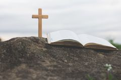 The cross and the bible is on the rock, sins and prayer. stock photos