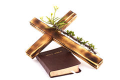 Cross and Bible  on white background. Wooden cross with thorny flower stem resting on a bible,  on a white background Royalty Free Stock Image