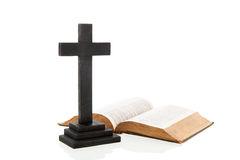 Cross and bible. Wooden black cross and open bible Royalty Free Stock Photo