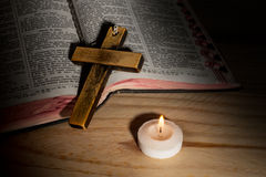 Cross on bible. On wooden boards in dim light Stock Photos
