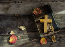 Cross on a bible. Wooden cross on a bible,leaves ,and dried flowers on a wooden table Royalty Free Stock Image