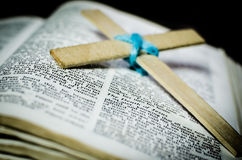 Cross and Bible. Wooden cross put on open Bible Stock Photo