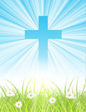 Cross on blue sky, with sun rays and green lawn Royalty Free Stock Photo