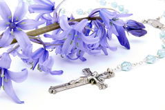 Cross and Bluebell. Bluebell with rosary beads in front on a white background Stock Image