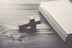 Cross and book. On a wooden table Stock Photos