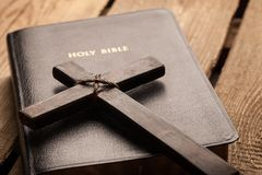 Holy Bible book and cross, close-up view. Cross book holy bible table background light stock photo