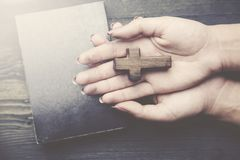 Cross, book and woman hand. Hands of Christian woman praying on wooden desk Royalty Free Stock Photos