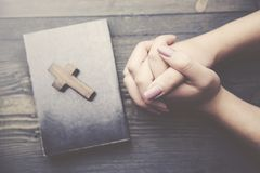 Cross, book and woman hand. Hands of Christian woman praying on wooden desk Stock Images