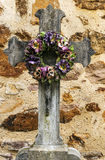 Cross with a bouquet of flowers. On a wall is a vertical picture Stock Photos