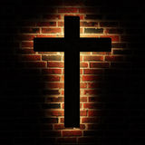 Cross brick. Wooden cross with the light on the brick wall Stock Photos