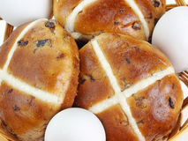 Cross buns. Closeup of basket with fresh hot cross buns and eggs Royalty Free Stock Images