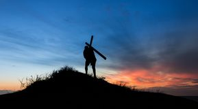 Cross Carring. Cross getting carried up a hill at sunet royalty free stock photo