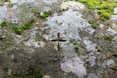 Cross carved in rock. With moss Royalty Free Stock Photo