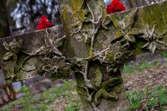 Cross at the cemetery with red flowers. Cross at the cemetery with flowers royalty free stock photography