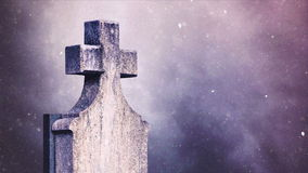Cross on the cemetery during snowfall stock footage