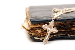 A cross with a chain against a old book Royalty Free Stock Photos