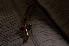 Cross on a chain in the Bible Royalty Free Stock Photography